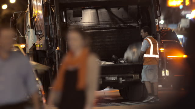 A garbage man catches trash and throws it into the back of a garbage truck in NYC at night