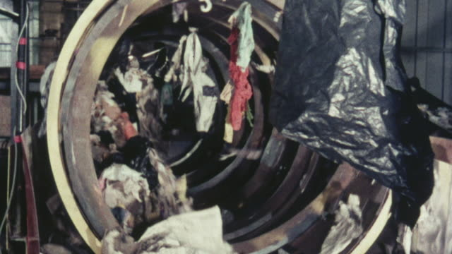 1976 MONTAGE Garbage spinning in a rotating screen while fine materials are discarded / Stevenage, Hertfordshire, United Kingdom