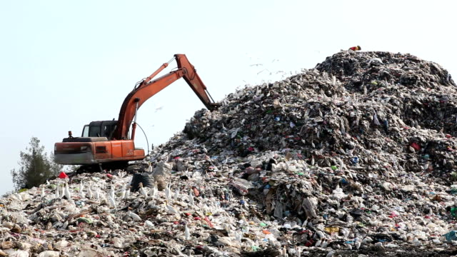 garbage truck moves trash in a landfill site, pollution, Global warming
