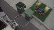 A garbage truck with a mechanical arm empties a trash container.
