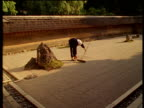 A gardener rakes patterns in gravel in the Ryoan-ji zen garden.