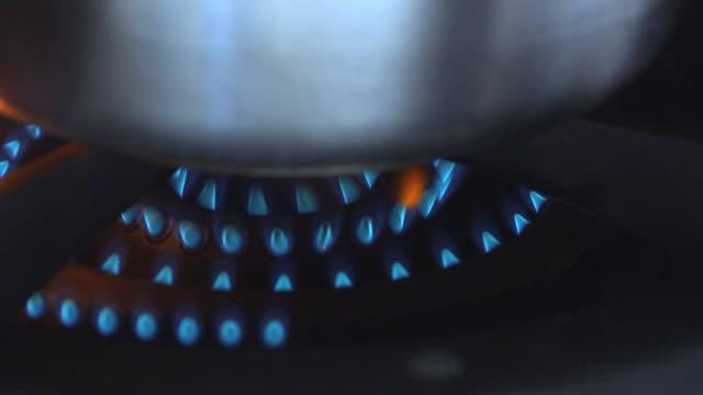 A gas burner heats a pot.