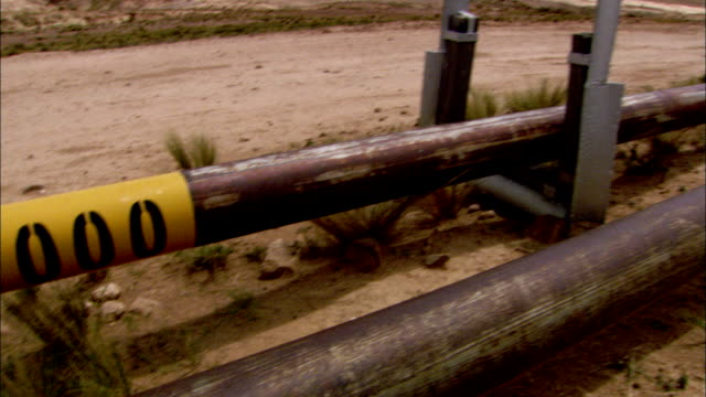 Gas pipes run parallel to a dirt road in a the Bolivian countryside. Available in HD.