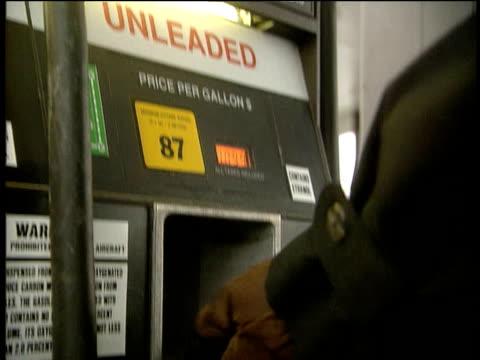 Gas Station attendant fills car with petrol Alaska