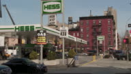 A Gas Station with high gas prices on a busy New York Street on 45th and 10th Avenue