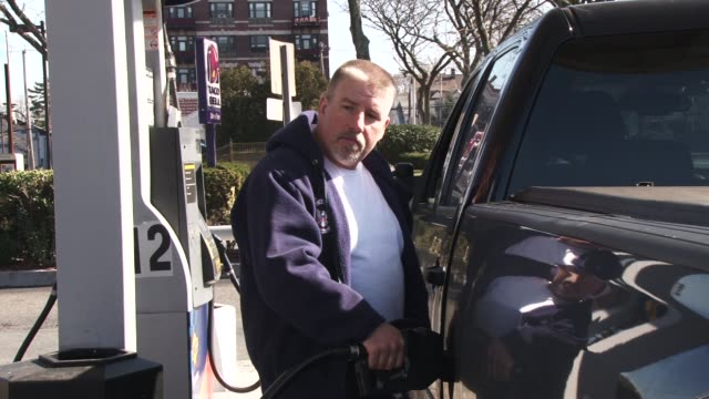 Gas stations in New York / Gas prices / Man fills his truck with gasoline / CU on gas prices and climbing total amount as gas is pumped / WS of...