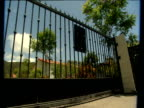 Gate opens across drive pool beside house and interior room of rehab clinic Malibu
