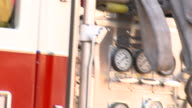 CU TU Gauges on side of fire truck/ CU Fire fighter sitting in truck and talking on headset/ Richmond, Virginia