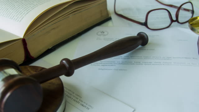 Gavel sitting on juridical paperwork contract
