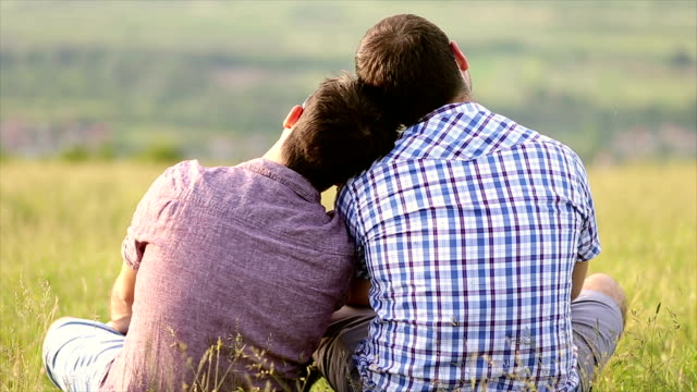Gay couple cuddling in the park