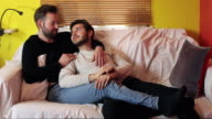 gay couple having a romantic chat on the couch
