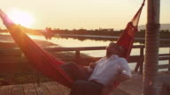 MS Gay couple in hammock on dock at sunset embracing and laughing
