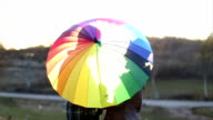 Gay couple kissing behind an multicolors umbrella