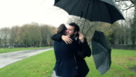 Gay couple meeting and hugging in the rain