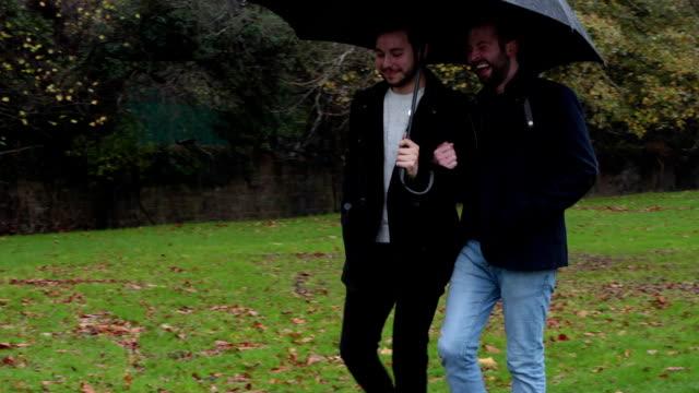 Gay di coppia condividere un ombrello Panning a sinistra