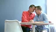 Gay couple sitting, talking