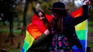 Gay Women Flirting Under Rainbow Flag in Nature