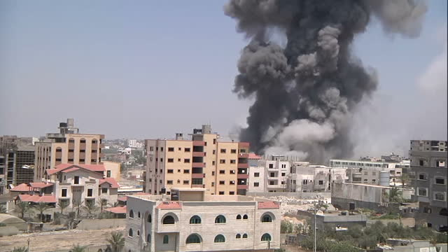 Gaza skyline with explosion behind apartment block and plume of smoke and dust rising into sky