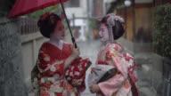 Geishas enjoying a talk while walking outdoors and holding an umbrella