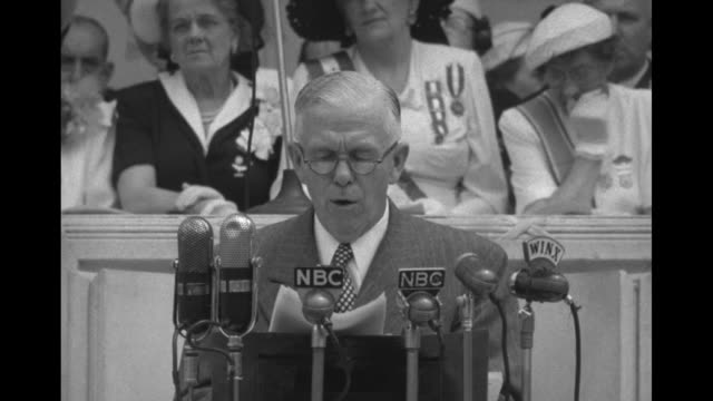CU Gen George Marshall wearing reading glasses and civilian clothing and looking at papers speaking behind microphones can see a few women seated...