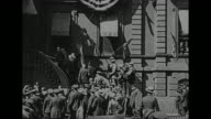 Gen John J Pershing arrives at elaborately decorated facade and climbs stairs to balcony hundreds of people with attempted crowd control by police...
