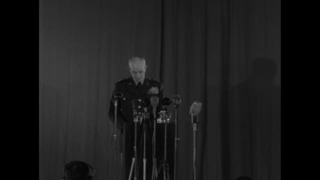 Gen Omar Bradley on stage behind microphones at NATO conference warning against reducing buildup of manpower as collective NATO defense because of...