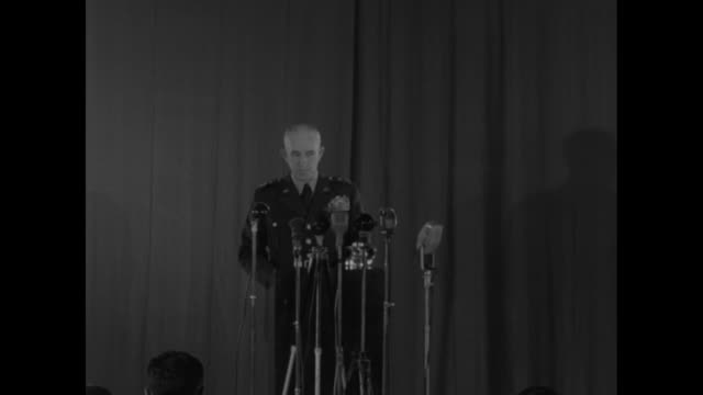 US Gen Omar Bradley speaking on stage behind microphones at conference he warns against putting too much faith in atomic weapons and reducing...