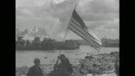 US General Douglas MacArthur accompanied by officers walking along beach / landing barges grounded near beach soldiers on beach US flag on pole stuck...
