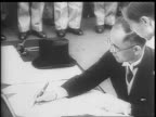 General Douglas MacArthur finishing speech at microphone / Mamoru Shigemitsu signs document surrendering unconditionally to the Allied Powers a...