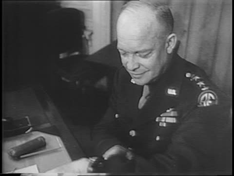 General Dwight D Eisenhower sits at desk and poses in front of a map / bombs explode around tanks at night / soldiers crawling across the ground at...