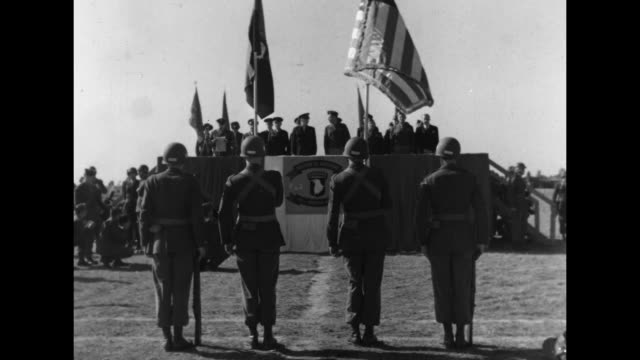 General Dwight Eisenhower on ground salutes United States Flag held by color guard / VS General on review stand watches troops march / Note exact day...