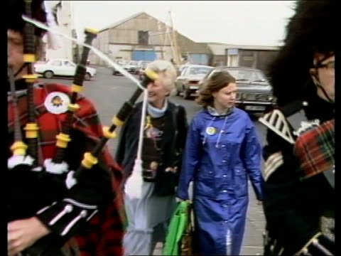 Orkney candidates EXT **Music heard SOT** Two Scottish pipers down street in front of Winnie Ewing Winnie Ewing waving at voters
