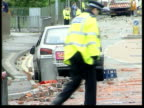 Oldham Car in street surrounded by bricks and debris from race rioting as policeman along past Man clearing bricks from pavement after rioting