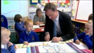 David Cameron primary school visit David Cameron seated with children at classroom desk helping them write postcards/ David Cameron talking with...