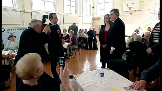 Labour Party Gordon Brown visit to Fife Pensioners Forum Gordon Brown writing message inside card for elderly man / Brown posing for photocall with...