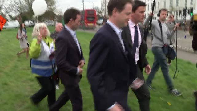 Campaigning Surrey Carshalton Nick Clegg with Liberal Democrat supporters along past crowd of protesters booing and chanting SOT Clegg into car as...