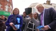 Boris Johnson campaigning in Hounslow ENGLAND London Hounslow EXT Boris Johnson posing for photos with man as campaigning / Johnson and others along...