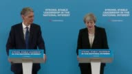 Theresa May and Philip Hammond joint press conference ENGLAND London Canary Wharf INT Theresa May and Philip Hammond along to podiums at press...