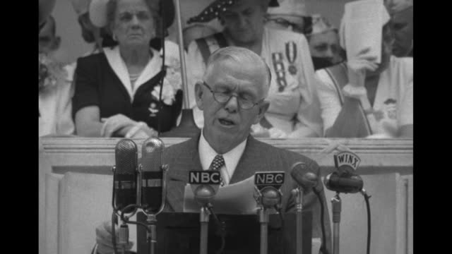 CU General George Marshall in civilian clothing and wearing reading glasses looks at papers as he speaks at podium behind microphones can see a few...