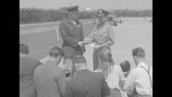 US General Henry 'Hap' Arnold stands with Maj Richard Bong US flying ace on airstrip they shake hands as rear shot photographers take photos / CU...