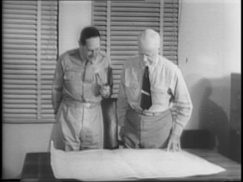 General MacArthur and Admiral Chester W Nimitz look over a map of the Pacific
