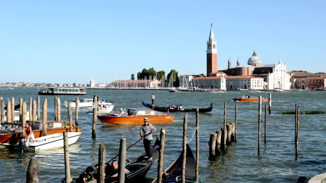 General view of boats and gondolas riding in Venice during a hot summer day