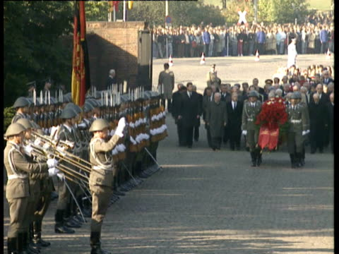 General view of wreath laying ceremony showing military band and soldiers slow stepping carrying wreath followed by Members of the Politburo...