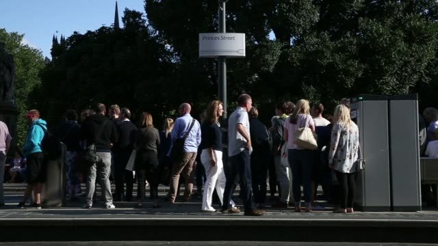 General views a crowd of people wait at the Princes Street tram station platform in Edinburgh UK on Saturday Aug 9 Passengers board a tram carriage...