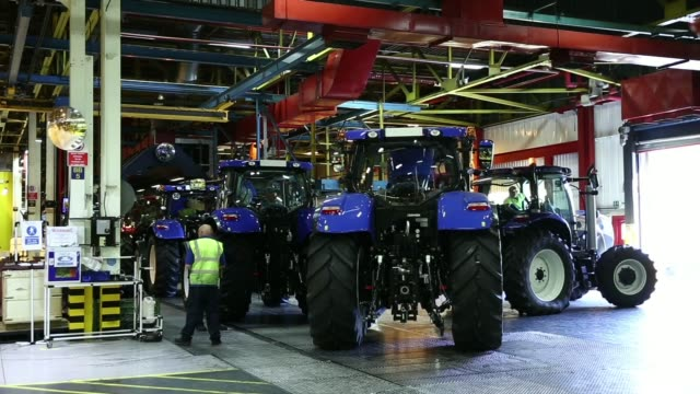 General views an employee performs final inspection checks on New Holland tractors at CNH Industrial NVs assembly plant in Basildon UK on Wednesday...