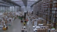 General views AO Warehouse Worker stacking boxes of microwave ovens on shelf using machine / Boxes of white goods stored in warehouse / Warehouse...