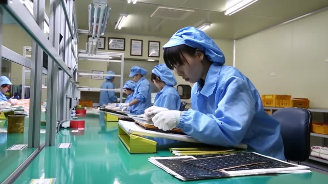 General views employees attach protective film to Flexible Printed Circuit Board panels on the production line at the Seil Electronics Co factory in...