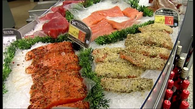 General views of Asda House and an Asda supermarket Close shots of fish on display at fishmonger counter / close shots of knife cutting fish / close...
