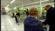 General views of Asda House and an Asda supermarket INT General views of checkout operators serving customers at tills inside Asda supermarket /...