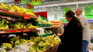 General views of Asda supermarket shoppers and produce Women buying bananas / Good close shots of boxes of bananas on shelf / Man putting white bread...